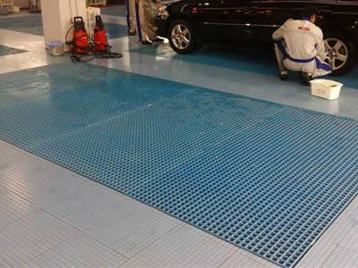 It shows in one carwash, many workers are washing the car, and the molded FRP grating is blue and matches the car size.