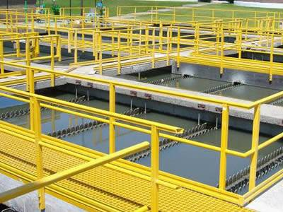 The picture shows that in a sewage disposal plant, there are yellow fiberglass grating walkways above the sewage.