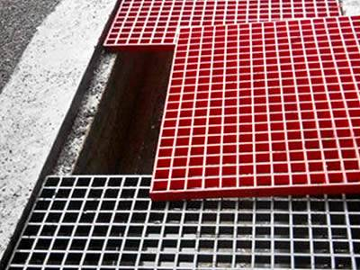 It shows that several pieces of molded FRP grating in red and gray are placed above the trench.