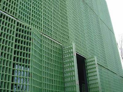 It shows many pieces of green FRP gratings that work as wall of a building.