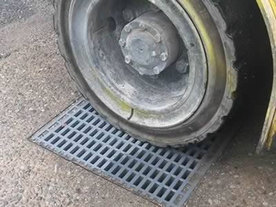 One piece of heavy duty fiberglass grating is installed above the drainage hole and one fork truck wheel is on it.