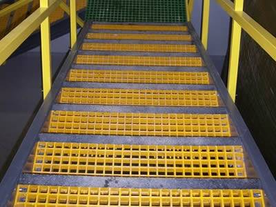 It shows the stairs indoors, and the treads are made of molded fiberglass grating in yellow and dark green.