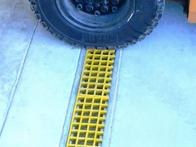 There is one auto tyre pressed on the yellow molded FRP grating trench cover.