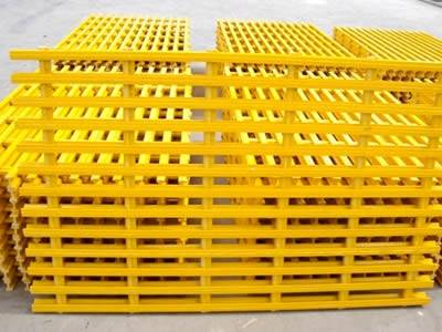 It shows several piles of pultruded fiberglass gratings in yellow, they have corrugated surface.