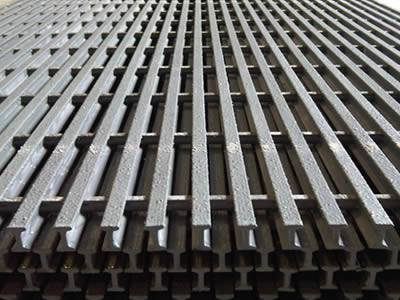 There are several piles of pultruded fiberglass gratings in gray, they have gritted surface.