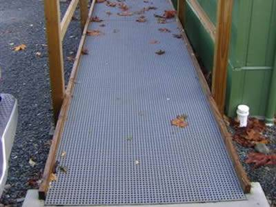 It shows that one wheelchair ramp fabricated with gray mini mesh FRP grating.