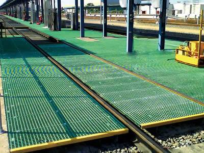 It shows green molded fiberglass gratings installed in the railway system.