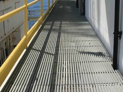 It shows the pultruded fiberglass gratings in gray are installed above the sea and there is handrail for protection.