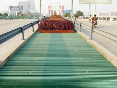 It shows that in the middle of the road, one green area is installed with green pultruded fiberglass grating.